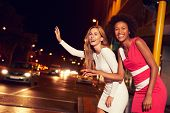 foto of hail  - Female friends hailing taxi on city street at night - JPG