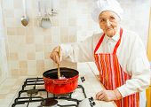 picture of kindness  - Kind grandmother preparing food in the kitchen - JPG