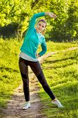 picture of leggins  - Young pretty woman exercising waist slimming stretch on a nature background - JPG
