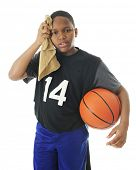 foto of tween  - A preteen basketball player hot and tired after a  rough game - JPG