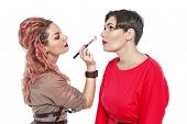 stock photo of makeup artist  - Professional makeup artist making makeup to a model isolated on white background - JPG