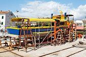 stock photo of dock  - old passenger boat under repair in dry dock - JPG