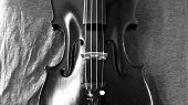 stock photo of violin  - Black and white closeup of violin against a linen background - JPG