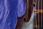 stock photo of violin  - Side of violin against a bright blue linen background - JPG