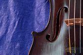 image of dark side  - Side of violin against a bright blue linen background - JPG
