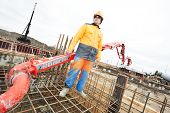foto of concrete pouring  - builder worker with boom pump pouring concrete on metal rods reinforcement of form work - JPG
