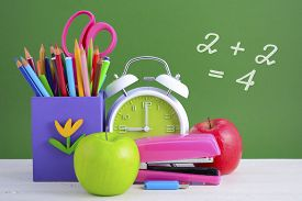 picture of classroom  - Back to School or Education Concept with classroom desk and bright colored stationery supplies on white wood rustic table and green board background - JPG