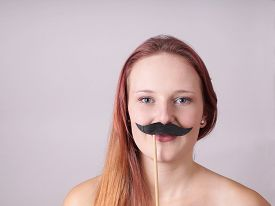 picture of crossdressing  - young woman holding a fake moustache on a stick to her face - JPG