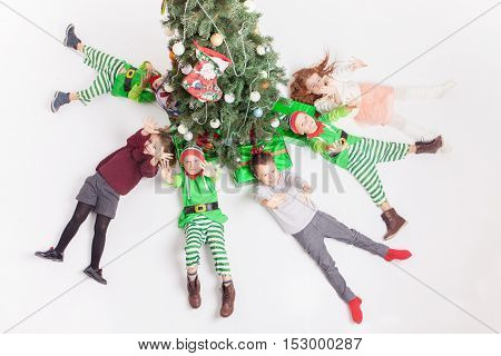 Merry Christmas 2016. Happy children celebrating Christmas lying near Cristmas tree. Kids dressed in elf costumes. A round dance, children's party Masquerade xmas. Aerial view