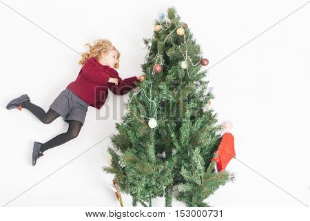 Portrait of flying little girl decorating Christmas tree, dressed in winter sweater. Angel. White background with copy space. Family decorating a Cristmas tree. Merry Christmas 2016
