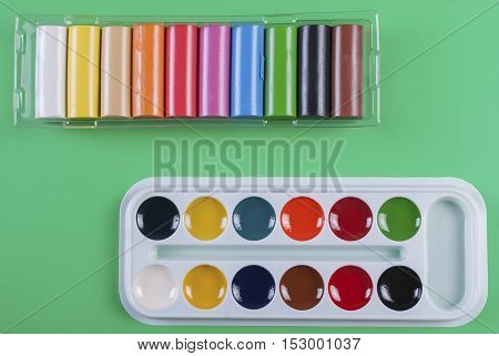 Watercolor paints and plasticine on a green background. For children's creativity