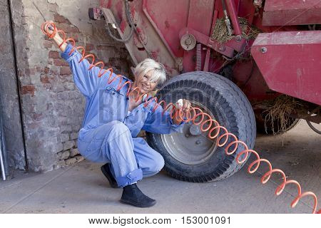 Mechanical Mature Female Inflates The Tire Of The Tractor