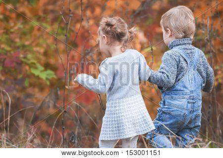 Happy children outdoor at fall season, holding hands. Has a date. Happy Family Values. Baby boy and girl. Children care. International Children's Day at 20 November or June 1 Universal Children's Day