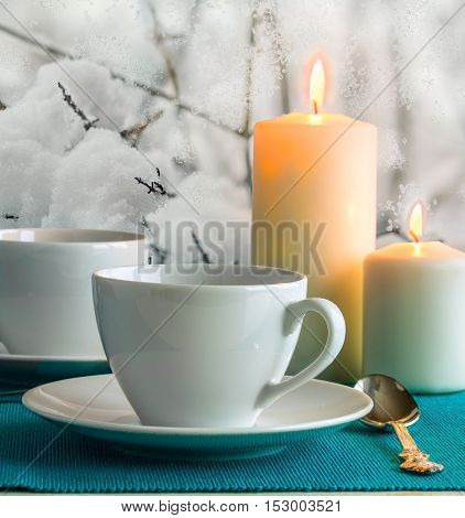 Two white cups and saucers two burning candles and a tea spoon on a turquoise napkin on the background of snow-covered garden outside the window in winter evening close-up