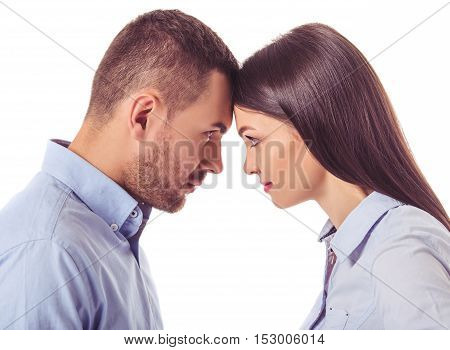 Side view of beautiful business couple in smart casual wear touching their foreheads and looking at each other isolated on white