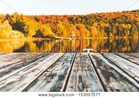 Empty wooden dock on the lake with trees on background. Old boards with a hook on the edge. Trees with typical autumn colours reflecting on the water. Relaxation nature and autumn themes.