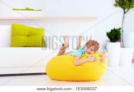 Excited Kid Having Fun On Yellow Bean Bag At Home