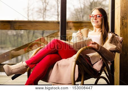 Woman Sitting On Chair Reading Book At Home
