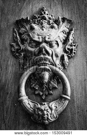 Vintage brass door knob on the wooden background.