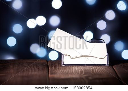 Professional blank business cards in holder stands on wooden table on a abstract dark background.