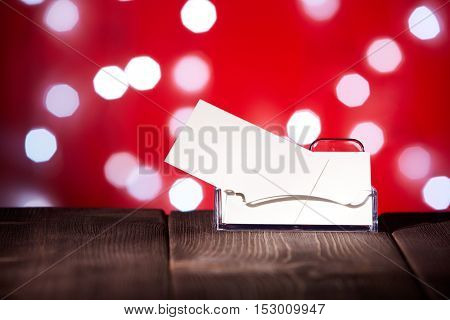 Professional blank business cards in holder stands on wooden table on a abstract red background.