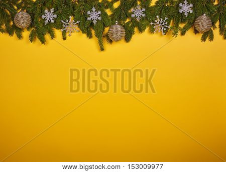 Yellow background with ornaments on fir tree branches. Chrismas and New Year.