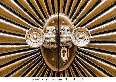Metal door shaped sunburst with round handles.