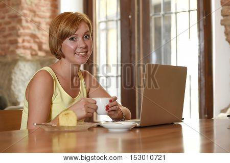 young beautiful and successful woman working or studying at coffee shop with laptop computer and enjoying cup of coffee for breakfast smiling happy and relaxed wifi connected to cafe internet