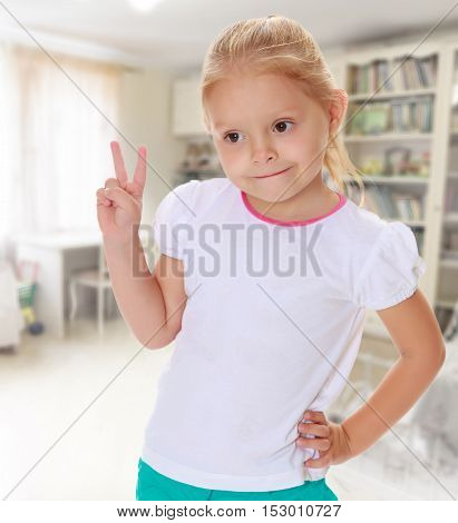 The concept of family happiness, and preschool education of the child , against a child's room with bookshelves.Cute little blond girl in white tank top without a pattern.Girl shows a sign of Victoria.
