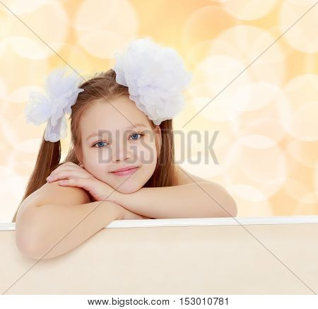 Gentle long-haired little girl with big white bows on the head . She leaned on the windowsill. Close-up.On a brown blurred background with white snowflakes.