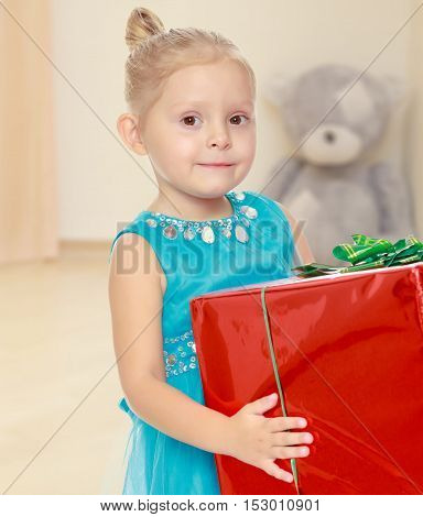 The concept of preschool development of the child , against a child's room where in the background a Teddy bear.Caucasian little girl in a blue dress, holding the hands of the big red box
