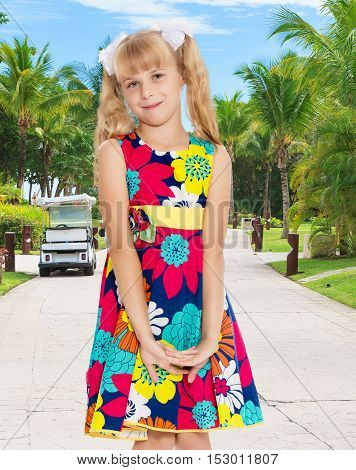Beautiful little girl with long blonde ponytails on her head tied with white bows, bright summer dress and knee socks.On the background of the road, palm trees and blue sky with clouds.