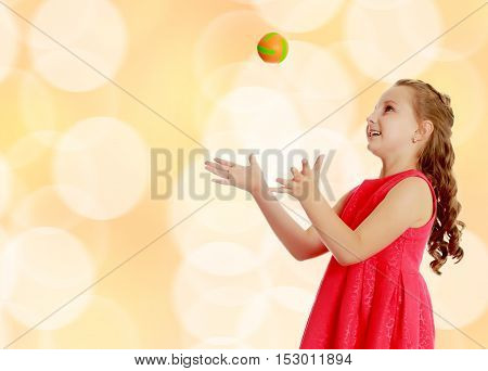Beautiful Caucasian little girl in a bright orange dress, throws a little ball.Brown festive, Christmas background with white snowflakes, circles.