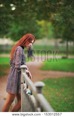 Elegant beautiful long haired girl with bright brown hair and a short dress stands on the bridge and looks down on the background of trees in the city Park.