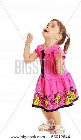 Pensive little girl with pigtails on the head , in a pink dress. The girl was looking at the top turned sideways to the camera.Isolated on a white background.