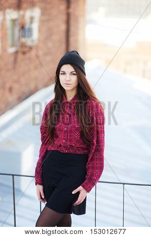 Portrait of a cute long-haired brunette girl with blue eyes in a red plaid shirt and black cap