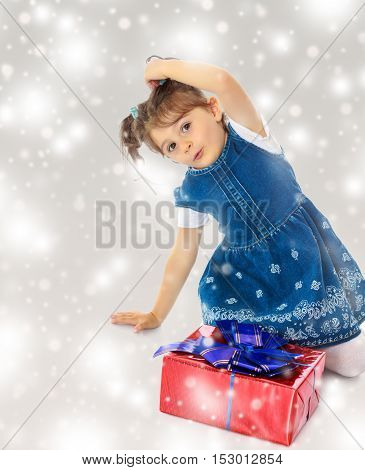 Charming little girl in a blue dress with short sleeves , kneeling around a red box with a blue bow.Gray background with round white snowflakes.