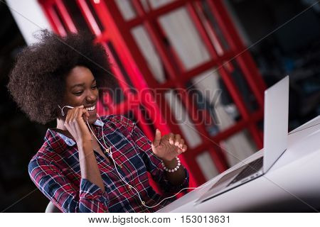 portrait of a young successful African American beautiful woman who enjoys spending a quality and joyful time while working in a large modern office
