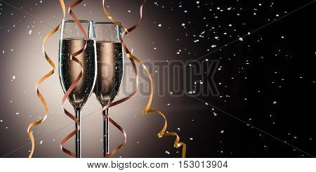Glasses with fizzing champagne, decorative ribbons and snow flakes closeup