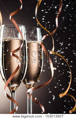 Two champagne glasses, decorative ribbon on dark background with snowfall