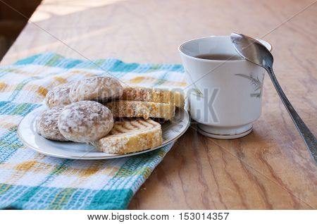 Spoon on a mug and saucer with cakes and rolls