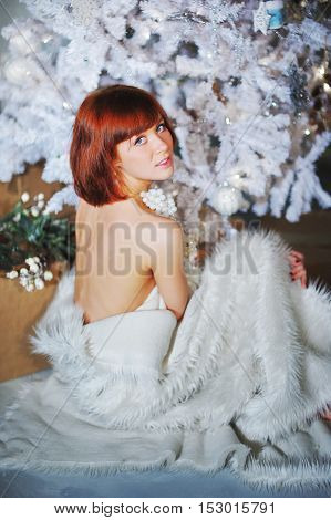 Christmas artificial tree with decoration and attractive smiling model in white fur Cape.