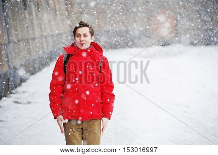 young handsome man in winter clothes enjoys the snow cold snowfall blizzard
