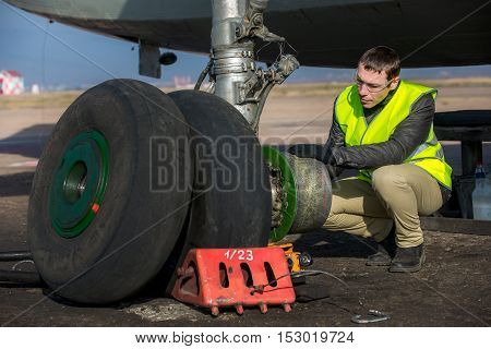 Male mechanic fixing airplane's wheels at airport