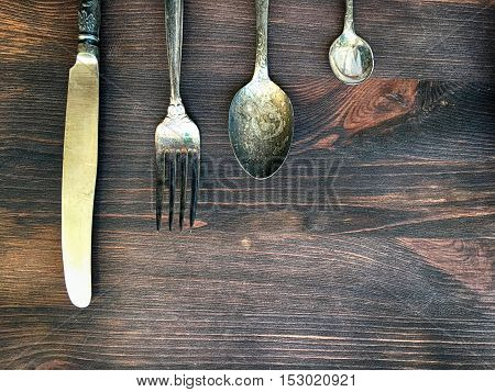 Old vintage knife fork and spoon on a brown wooden background top view