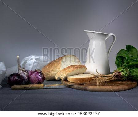 still life. jug, bun, onion garlic on a blue tablecloth