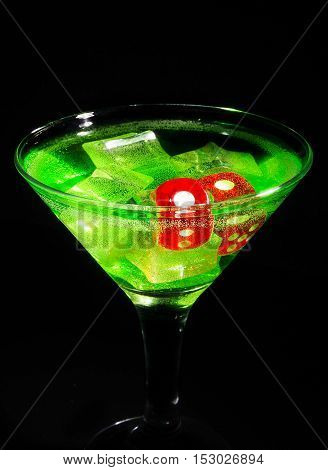 Red dice in a cocktail glass on black background. casino series.