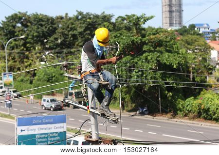 KOTA KINABALU, SABAH MALAYSIA - OCT 19,2016: Unidentified electircian repairing the overhead line fuse on top of electric post power pole