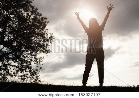 A happy asian woman is relaxing on green grass and raised up to sky arms on sunny summer day with park background. Concept of well being and healthy lifestyle. Relaxing concept.