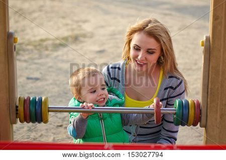 Mother and son on playground in autumn park. Family time. Happiness of childhood and parenthood. Outdoor Activities.
